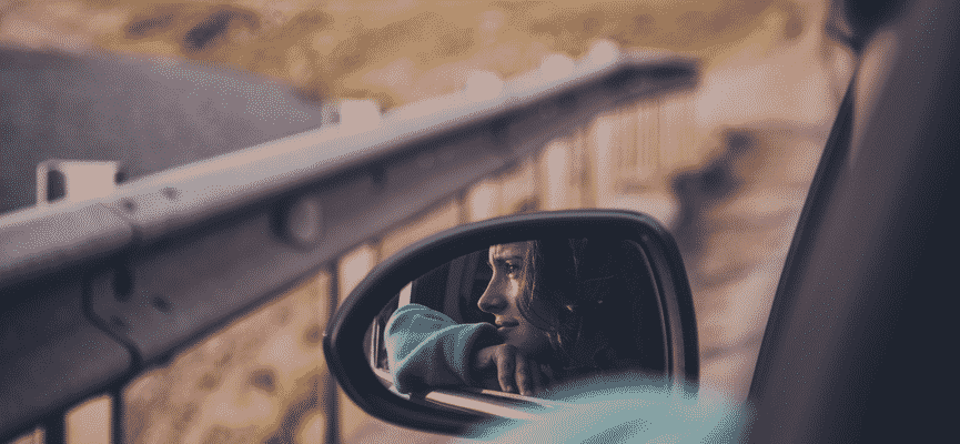 girl's reflection in car mirror